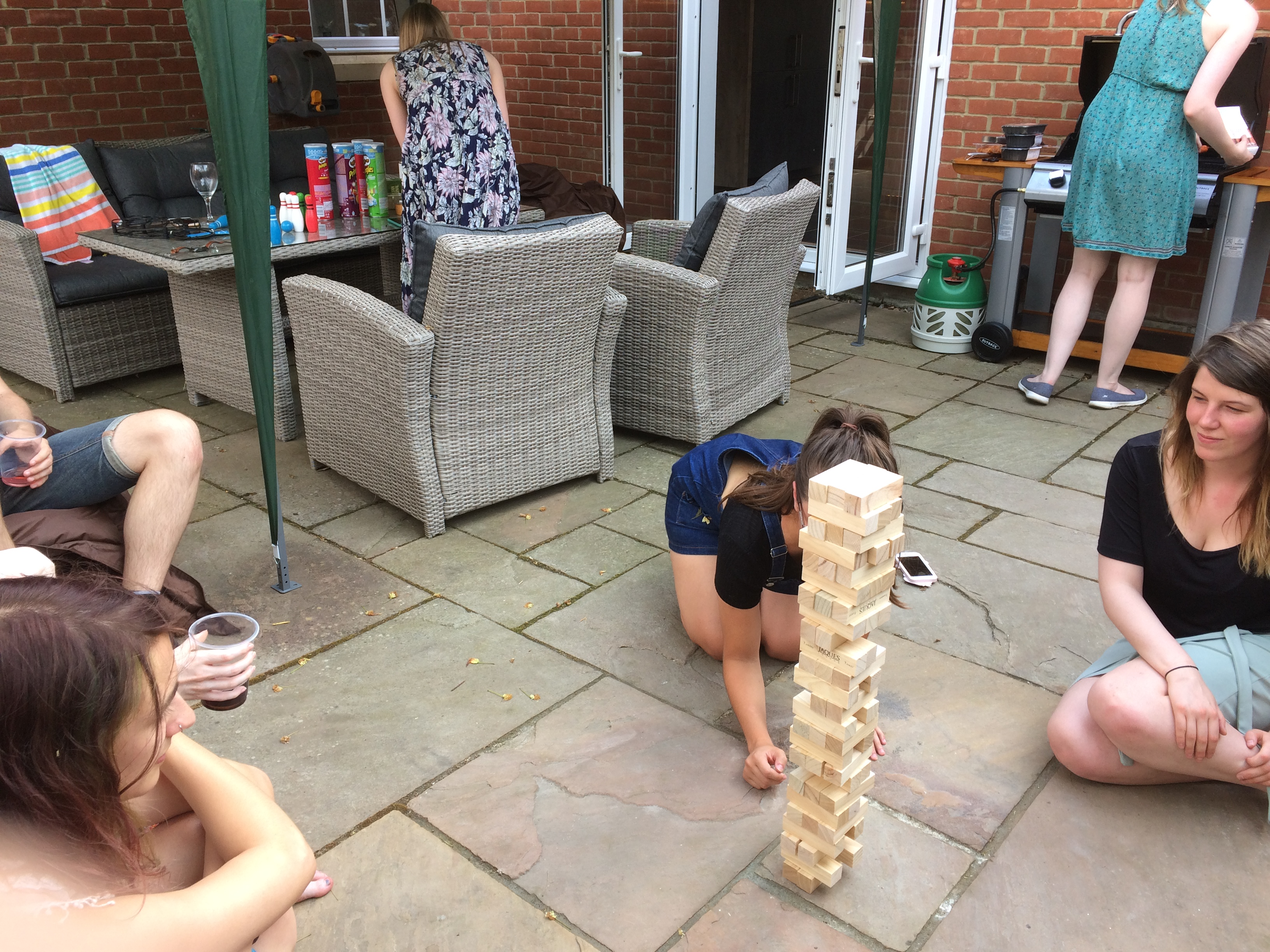 Group of people playing garden tumble tower on the patio