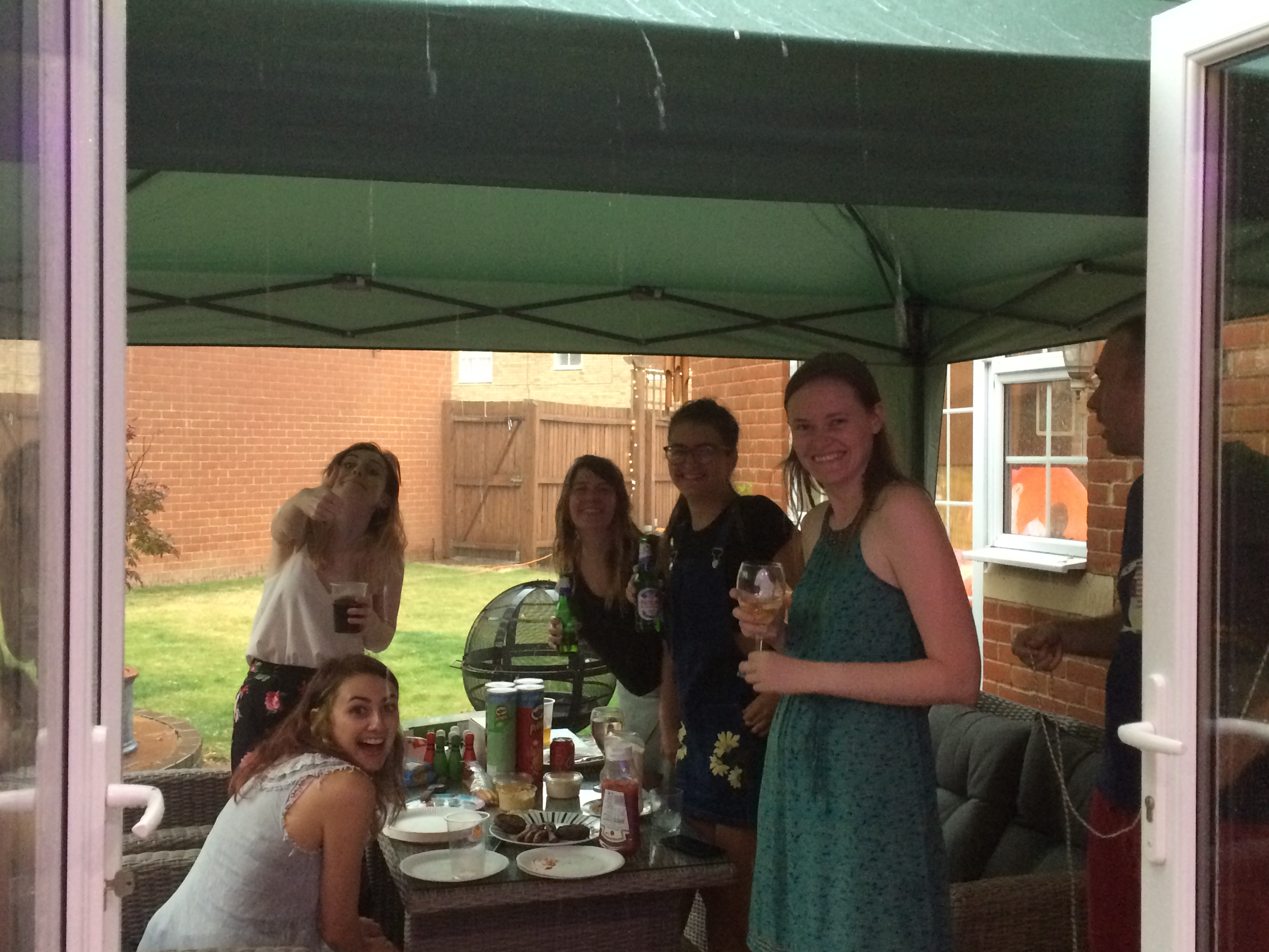 Group of us happily gathered under the gazebo as rain pours outside