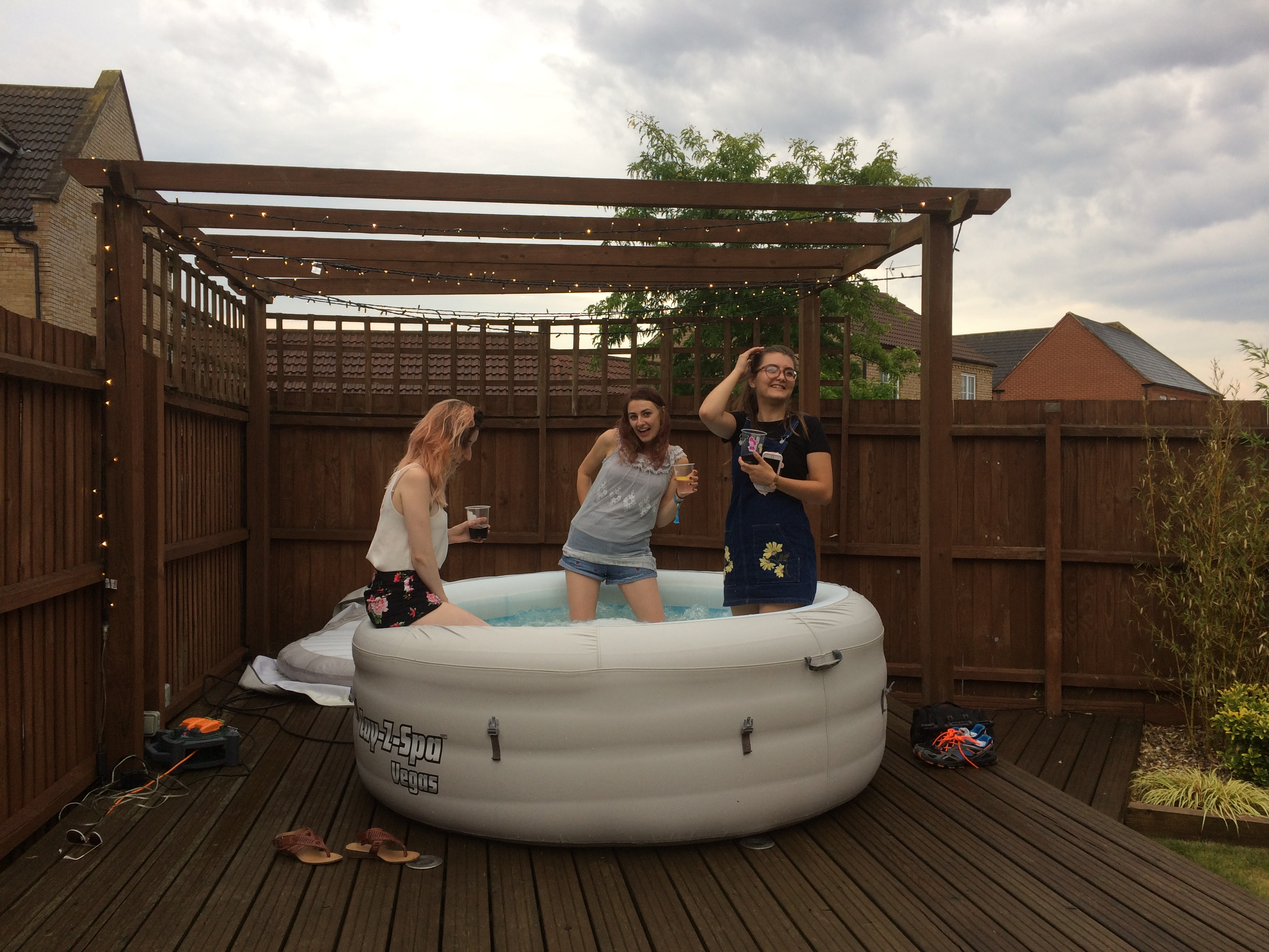 Alice, Lauren and Berni perched at the edge of the hot tub with their legs in the water, under a grey sky