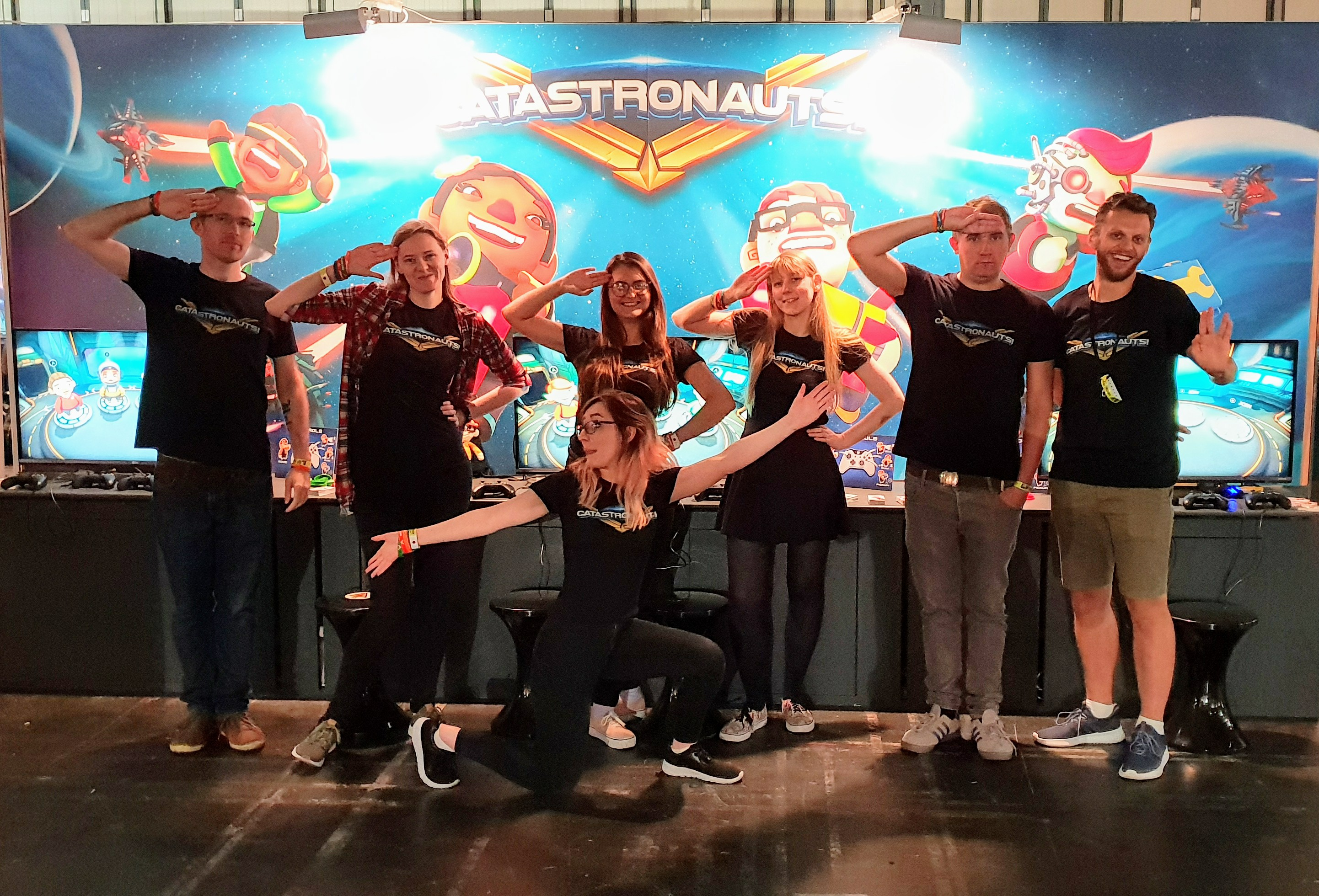 The group of us doing funny poses (mainly salutes) in front of our EGX stand, wearing Catastronauts t-shirts