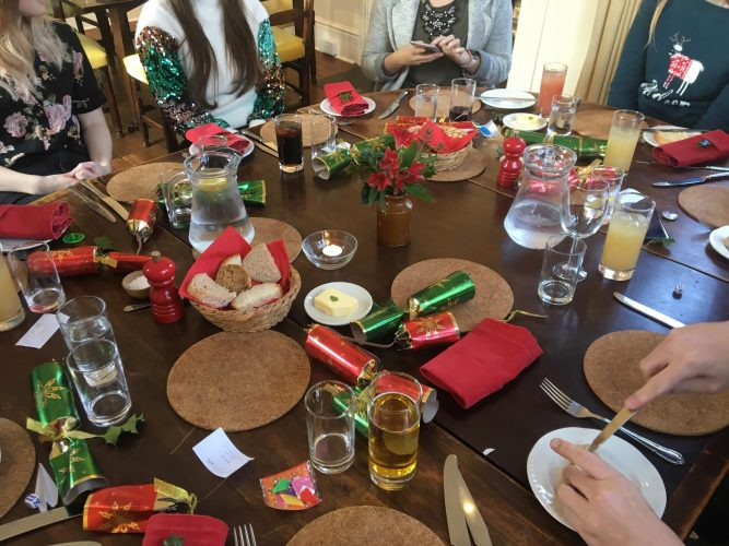 A round wooden table covered in cork placemats, glasses of various drinks and red and green napkins, Christmas crackers and flowers. People are seated around the edge wearing Christmassy clothes