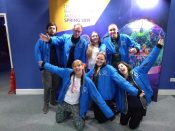 The Inertia team in blue Crystal Maze bomber jackets, posing with excited expressions (except two men who look confused) and arms out, in front of a picture of the Crystal Dome.