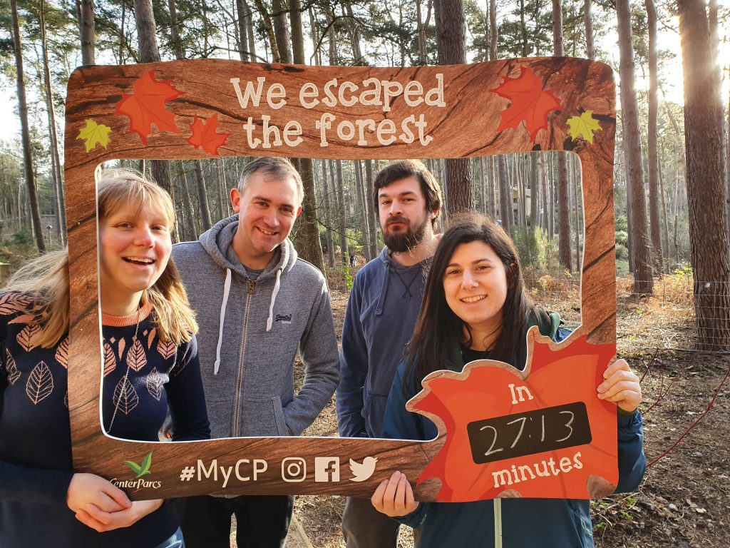 "Four people smiling inside a large frame they are holding. It's decorated in a forest theme with ""We escaped the forest in 27:13 minutes"" written on it and the Center Parcs logo."