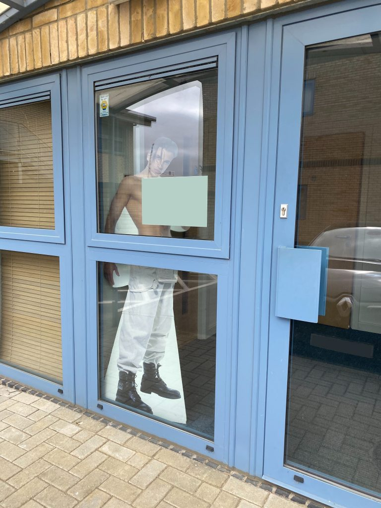 A glass office door with a Peter Andre cardboard cutout inside.