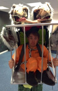 Graeme dressed as a two headed dinosaur carrying a cage with a convict in (yes, it's a very complicated costume)